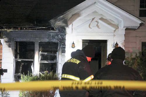 Officials with the Suffolk County Arson Squad begin their investigation of a fatal house fire in Greenport Wednesday night. (Credit: Paul Squire)