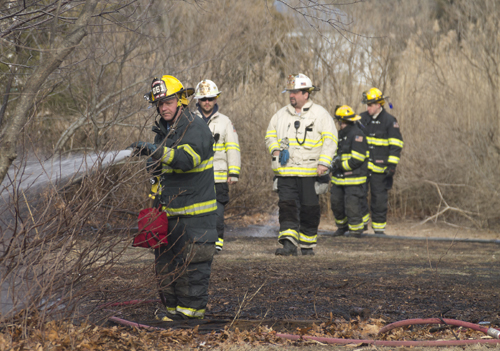 Mattituck firefighters douse the last of a small brush fire on Bay Avenue Thursday afternoon. (Credit: Paul Squire)
