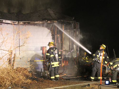 PAUL SQUIRE PHOTO | Cutchogue firefighters douse a Cutchogue house after it was destroyed by fire early Wednesday.