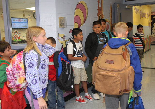 Southold Elementary School gather in the lobby before the official start of school Tuesday, some with very large bakpacks.