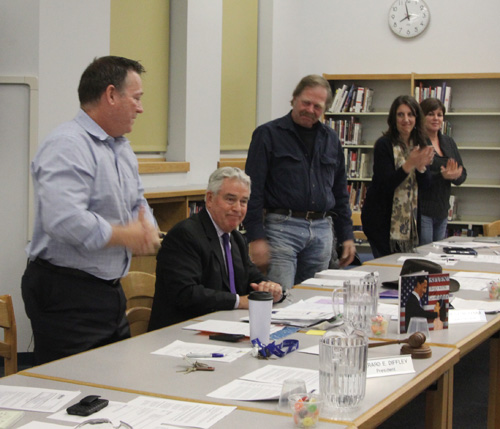 The Mattituck school board applauding Superintendent James McKenna moments after he announced his plans to retire.