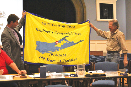 JENNIFER GUSTAVSON PHOTO | Mattituck High School principal Shawn Petretti (left) and school board member Doug Cooper unveil the centennial class's flag. The 2014 commencement will take place June 21.