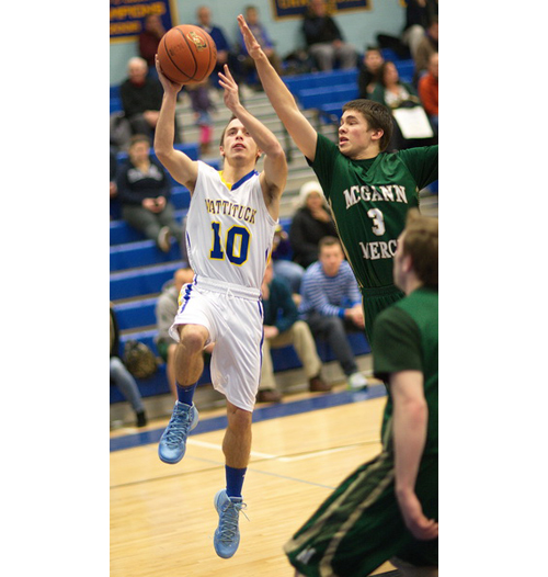 GARRET MEADE PHOTO | Mattituck sophomore Joe Tardif, putting up a shot while being guarded by Bishop McGann-Mercy's Greg Gehring, scored a career-high 24 points with the aid of four 3-pointers.