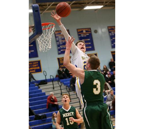 Mattituck's Ryan Mowdy blocking a shot while Bishop McGann-Mercy's Eddie Kneski (15) and Joe Jeskie (3) watch. (Credit: Garret Meade)