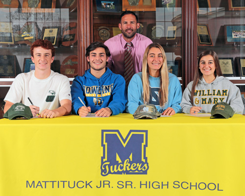 Mattituck athletic director Gregg Wormuth oversees a ceremony in which four players from the Mattituck/Greenport/Southold boys and girls lacrosse teams signed national letters of intent. The players, from left, are Tim Schmidt, Zach Holmes, Katie Hoeg and Audrey Hoeg. (Credit: Daniel De Mato)