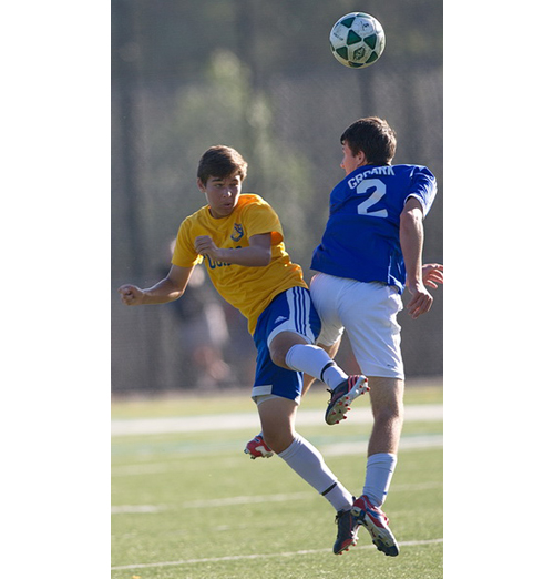 GARRET MEADE PHOTO | Mattituck's James Hayes in an aerial duel with Elwood/Jophn Glenn's James Groark.