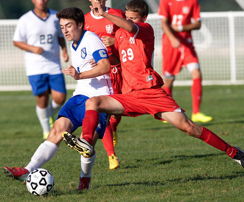 Mattituck midfielder John Batuello, left, is challenged by Center Moriches midfielder Anthony Mascia. (Credit: Garret Meade)