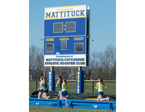 Runners in the 1,500-meter race pass the scoreboard near Mattituck's new track on Monday. (Credit: Robert O'Rourk)