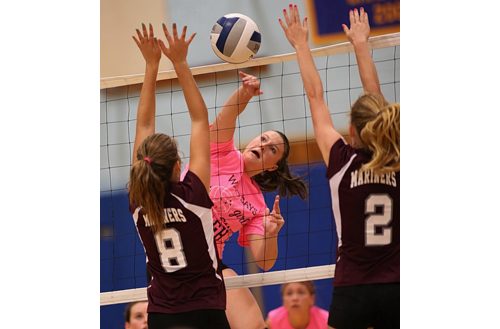 Emilie Reimer, who had 10 kills for Mattituck, found room to hit the ball between Southampton's Maddy Elliston (8) and Lexi Rusko. (Credit: Garret Meade)