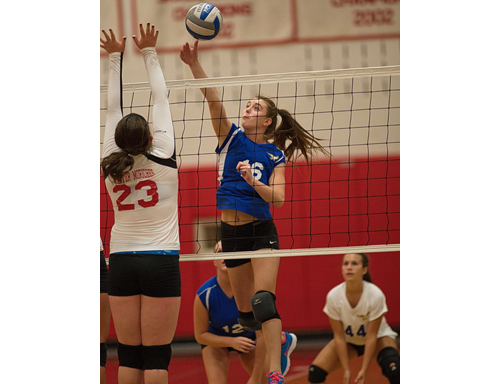 GARRET MEADE PHOTO | Mattituck middle hitter Shannon Dwyer tries to direct the ball past an attempted block by Center Moriches' Caroline Casey.