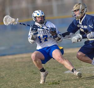 GARRET MEADE PHOTO   Connor Stumpf of Mattituck/Greenport/Southold craddling the ball while Bayport-Blue Point's Austin Belz shadows him.