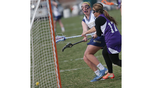 Mattituck/Greenport/Southold's Molly Kowalski gets off a shot despite the efforts of Hampton Bays' Paula Cardenas. (Credit: Garret Meade)