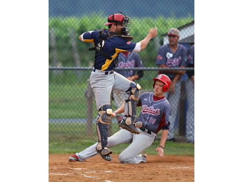 The North Fork Ospreys Catcher Sean Buckhout #9 leaps for a high throw as Montauk's Ryan Markey #10 scores a run at Jean W. Cochran Park in Peconic on July 30, 2016.