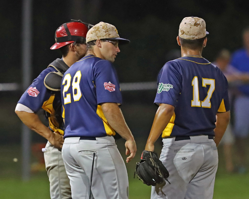The North Fork Ospreys pitching coach Casey Schuermann #28 talks with Pitcher Brandon Alberto #17 and catcher Sean Buckhout #9 during the game against the Montauk Mustangs at Jean W. Cochran Park in Peconic on July 30, 2016.