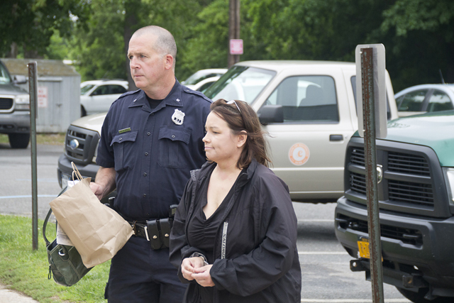 Nuria Russell is escorted into Southold Town Justice Court Tuesday. (Credit: Paul Squire)