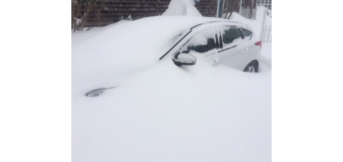 A car is buried in snow in Orient Tuesday. (Credit: Troy Gustavson)