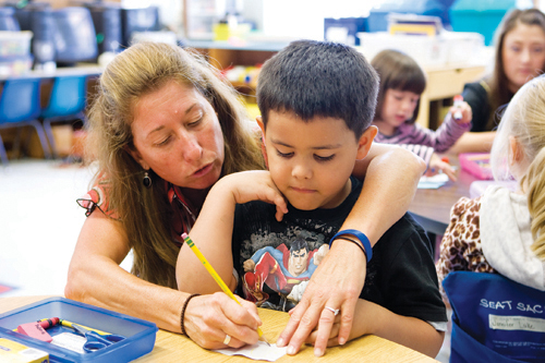 KATHARINE SCHROEDER FILE PHOTO | In a 2010 photo, Oysterponds teacher Jenny Schoenstein helps a kindergartner with a writing exercise. Her name is listed with other teachers expected to be laid off June 30.