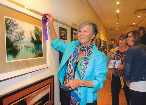 Gail Gallagher of South Jamesport pins the 'Best of Show' ribbon on a photo she took three years ago on a trip to Vietnam during the 51st annual Photography Show at Riverhead Free Library Friday evening. The Friends of the Library show was dedicated to Thelma Booker, who has spearheaded the show since 1999. (Credit: Barbaraellen Koch)