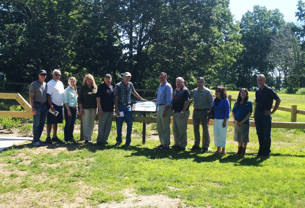 County and town officials met Monday morning to celebrate the completion of the Bay Avenue rain garden. (From left to right) Allan Connell, USDA-NRCS, Peter Young, Town of Southold Conservation Advisory Committee, Sarah Cote, Town of Southold, Sharon Frost, Suffolk County Soil & Water Conservation District, Gerry Goehringer, Mattituck Park District Commissioner, John Bredemeyer, Southold Town Board of Trustees, Al Krupski, Suffolk County Legislator, Jamie Richter, Town of Southold Engineer, Michael Collins, Town of Southold Civil Engineer, Elizabeth Condon, Suffolk County Soil & Water Conservation District, Polly Weigand, Suffolk County Soil and Water Conservation District, and Jeff Standish, Town of Southold Public Works. (Credit: Courtesy)