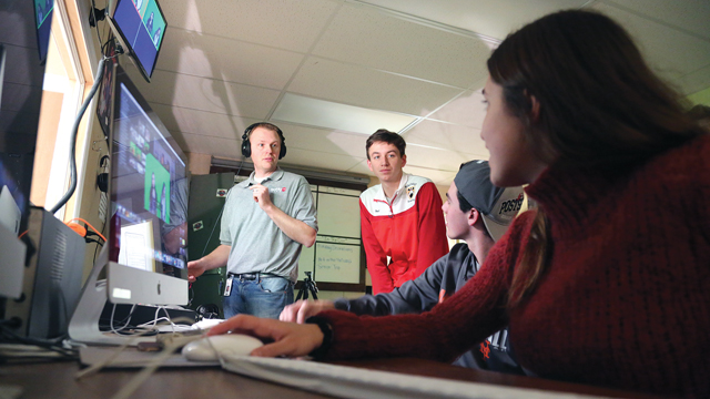 Class advisor Jason Wesnofske, left, helps students edit news packages last Thursday afternoon in their SOHO TV class at Southold High School. (Credit: Krysten Massa)
