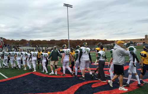 The Bishop McGann-Mercy and Shoreham-Wading River teams exchange handshakes following Saturday's playoff game at Miller Place High School. (Credit: Bob Liepa)