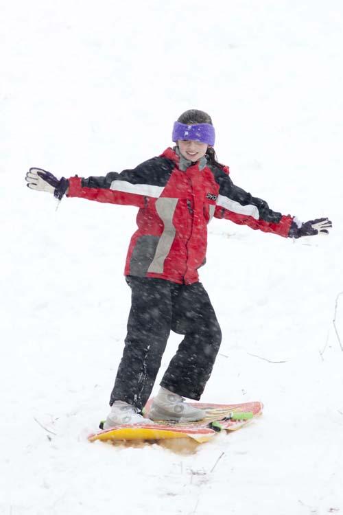 KATHARINE SCHROEDER PHOTO | Twelve-year-old Katie Parks of Cutchogue snow-surfs down the sledding hill in Mattituck.