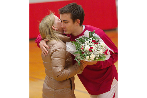 GARRET MEADE PHOTO | Kenji Fujita, one of Southold's six seniors, hugs his mother during a pregame Senior Night ceremony.