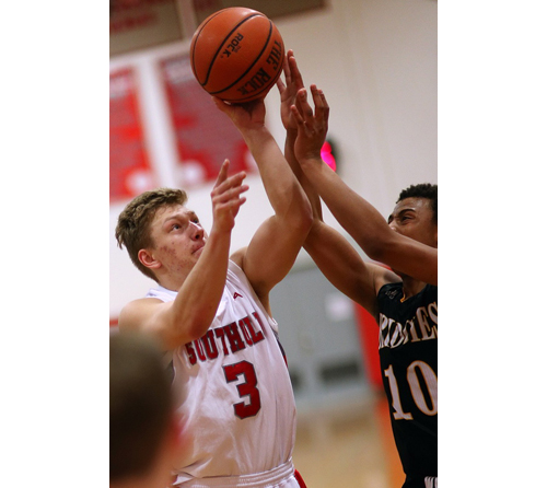 Pat Mejsak, who scored 10 points for Southold, is challenged by Bridgehampton's Tylik Furman while attempting a shot. (Credit: Garret Meade)