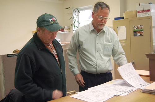 Town Trustee Jim King (left) reads over a permit application alongside Trustees president John Bredemeyer. After 20 years on the board, Mr. King will not seek re-election in November. (Credit: Cyndi Murray)