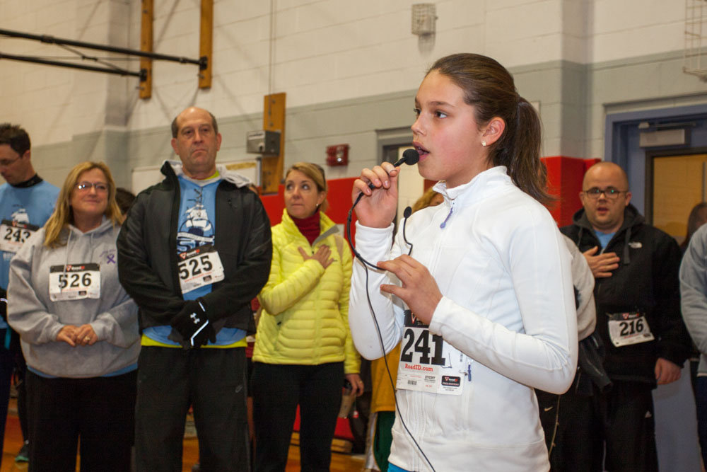 Southold 6th grader Juliet Rand sings the Star Spangled Banner before the race.