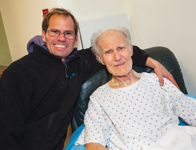 Jeff Heidtmann and the man he rescued, Robert Frey, pose for photos last January, when they were reunited for the first time after Mr. Heidtmann pulled the older man from the icy waters of a canal behind the neighbors' Southold homes. Mr. Frey has no memory of falling in or being pulled from the canal. (Credit: Paul Squire)