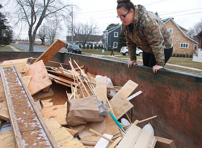 Ms. Horton jumps up on a dumpster looking for metal discarded during a house renovation in Greenport. (Credit: Cyndi Murray)