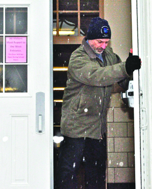 GIANNA VOLPE PHOTO  |  Mattituck High School security guard Gary Spath secures the doors after school Tuesday.
