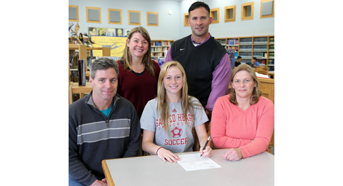 Mattituck senior Nikki Zurawski, sitting between her parents John and Patricia, signed a national letter of intent for Sacred Heart University. Mattituck coach Malynda Nichol and athletic director Gregg Wormuth also participated in the signing ceremony. (Credit: Garret Meade)