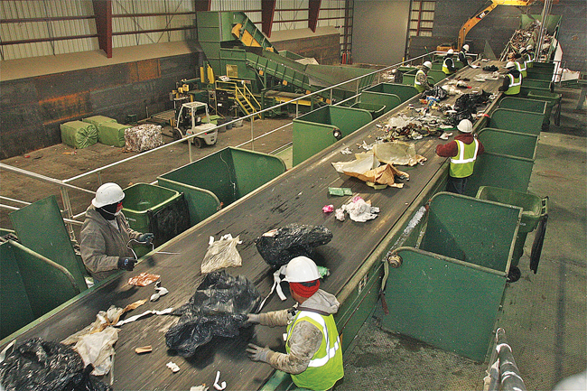 Peconic Recycling workers sort through garbage as it comes down the conveyor belt Monday morning. (Credit: Barbaraellen Koch)