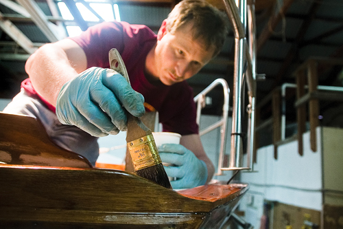 Brewer Yacht Yard & Marina worker Eric Scharpf applies varnish to a Cape Dory-brand sailboat in the Greenport yard's maintenance area. (Credit: Paul Squire)