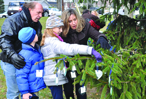 TIM KELLY FILE PHOTO | Thomas Calendrillo (left) his sister, nancy Daab, and her children, Celine and Alan, found an ornament bearing the name of the children's grandfather, Joseph Calendrillo at East End Hospice's Tree of Lights on the Cutchogue Village Green in December.