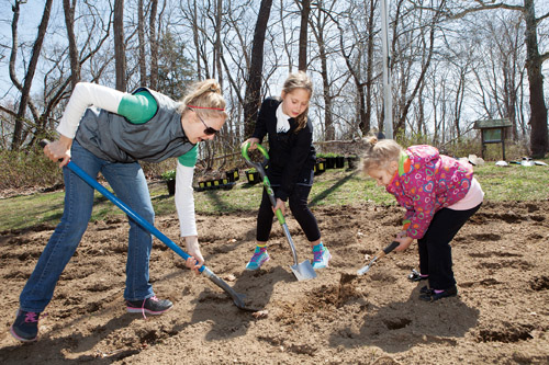 Group for the East End's Missy Weiss prepares soil with Victoria Witczak, 9, of Cutchogue, and her sister Julianna, 3, last weekend at Downs Farm Preserve in Cutchogue.