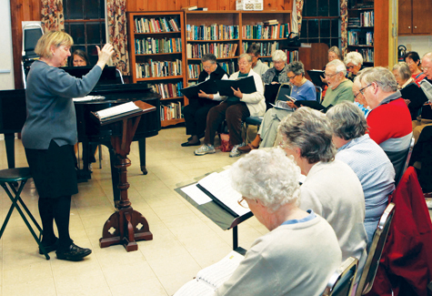 Lois Ross, left, leads the choir at a 2011 practice session of North Fork Chorale.