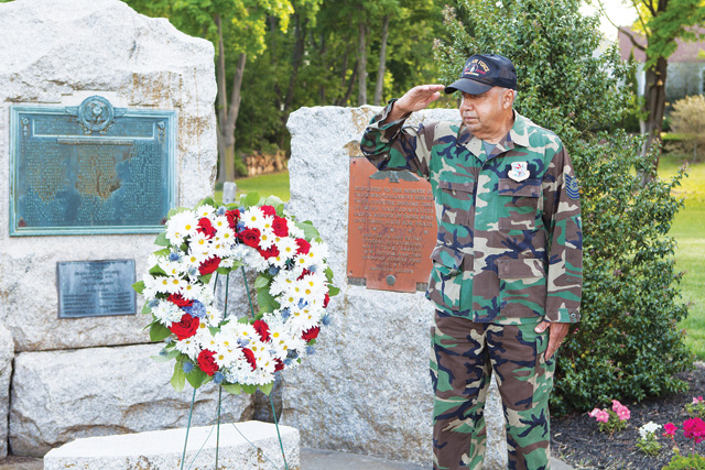 Master Sgt. LeRoy Heyliger salutes a wreath placed at the Mattituck war memorial on Memorial Day. Mr. Heyliger, a former member of Mattituck Veterans of Foreign Wars Post No. 11117, said he and other members were encouraged to join the Southold American Legion when the the Mattituck VFW post folded two years ago. He said he didn't know why they weren't encouraged to join the Mattituck Legion. (Credit: Katharine Schroeder)