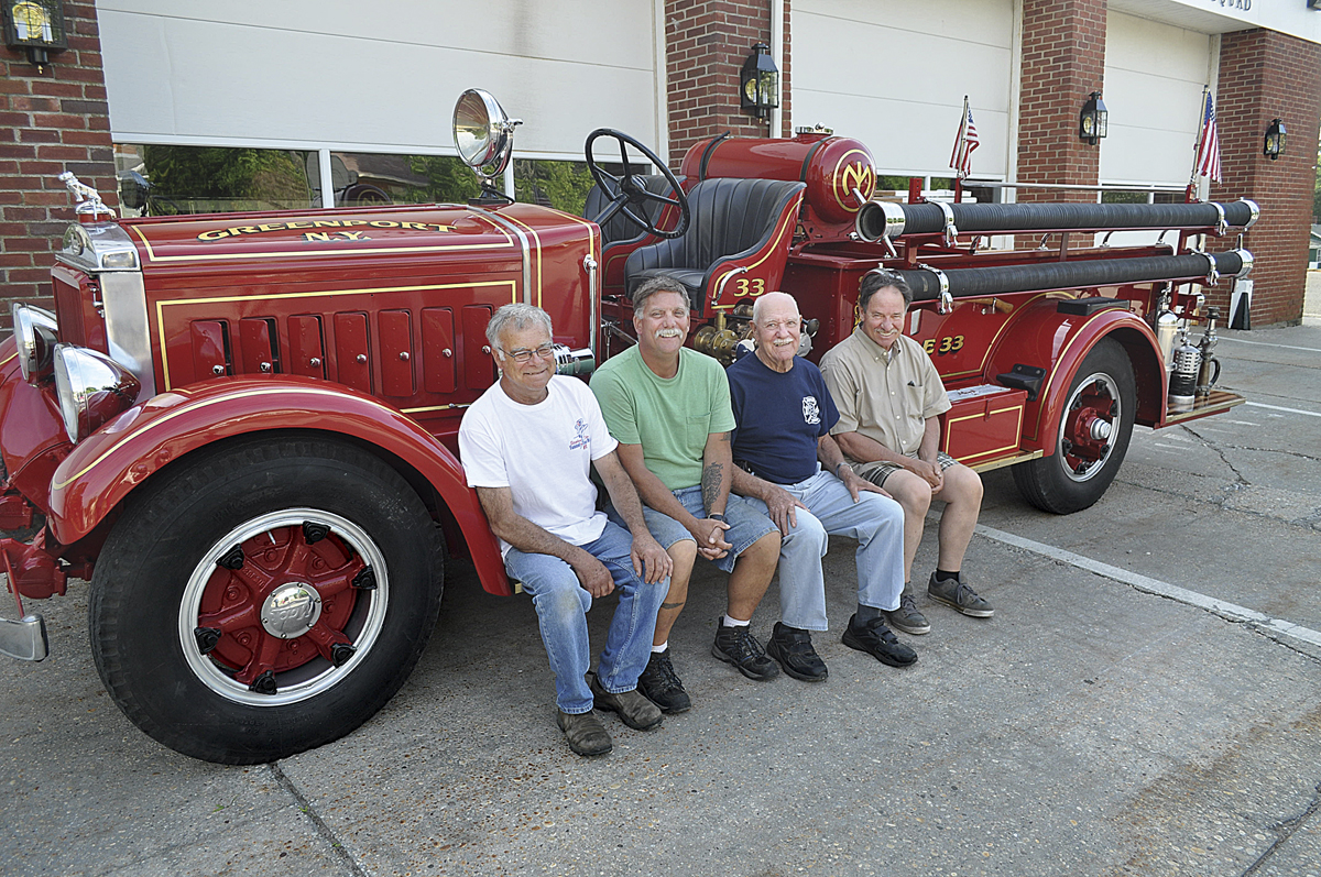 For the past 2 1/2 years, four Greenport Fire Department members have led the effort to restore the company's 1933 fire truck. Bob Jester (from left), John Grilli, George Capon and Charlie Hydell took it for its first test drive last month. (Credit: Grant Parpan)