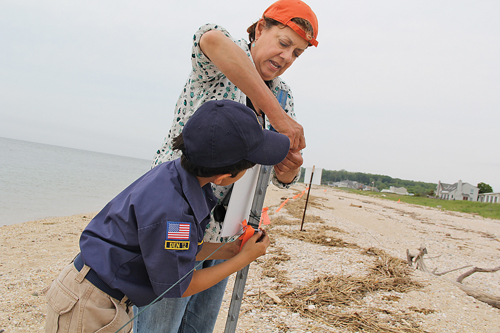 North Fork Audubon Society volunteer Diana Van Buren helps Gabriel Perez Colombo, 8, of Cutchogue hang his handmade sign at a Kenney's Beach nesting area last Wednesday. (Credit: Carrie Miller)