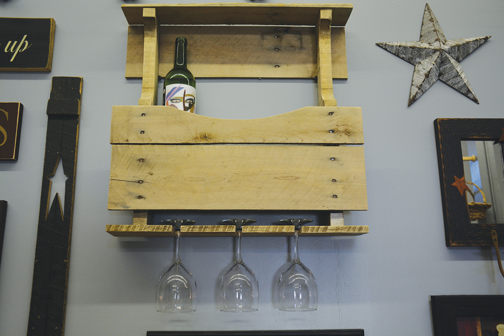 A wooden pallet, upcycled as a wall wine and glass holder.