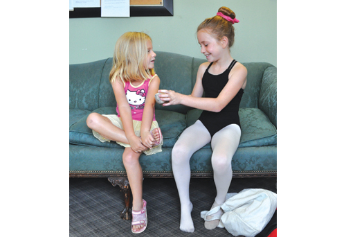 Aela (right) expains the different types of ballet shoes to her 5-year-old sister, Paige. (Credit: Rachel Young)