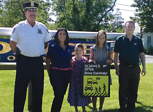 Southold police Chief Martin Flatley joined AAA traffic safety program coordinator Gerri DiSalvo and students Ciatlin and Mackenzie Jacobs and AAA community transportation specialist Christopher McBride to warn drivers to drive carefully. (Credit: AAA New York)