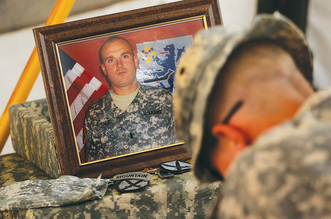 A soldier in the 1-71st Cavalry of the 10th Mountain Division bows during a memorial service for Lt. Joseph Theinert in June 2010 at the patrol base in Belanday, south of Kandahar, Afghanistan. (Credit: Chris Hondros/Getty Images)