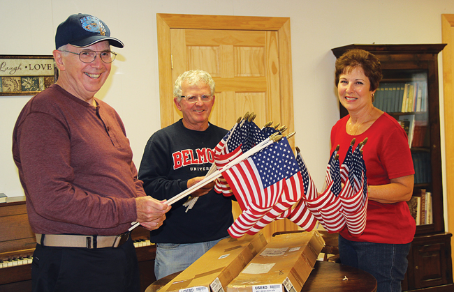 Barbara McAdam (right) sorts flags with the help of her husband, Tom (left), and Cutchogue United Methodist Church Pastor Richie King. Each flag will be fitted with a ribbon bearing a veteran's name and service information. Donations for more than 75 flags have already been collected. (Credit: Carrie Miller)