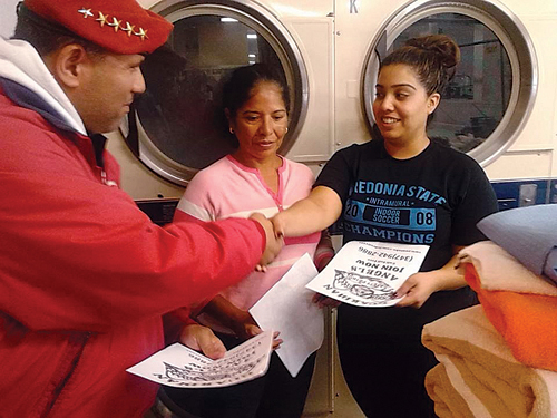 Guardian Angel Benjamin Garcia talks with two women at a Greenport laundromat Monday night. (Credit: Guardian Angels)
