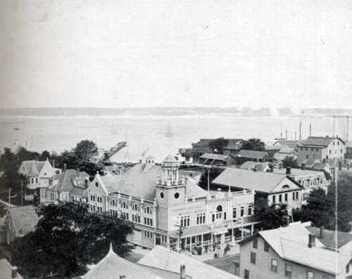 This undated aerial shot of the east side of Greenport Village's commercial district features the Greenport Opera House as the focal point. (Credit: Postcard History Series)
