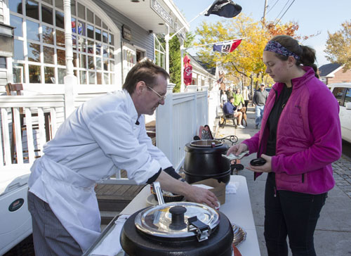 KATHARINE SCHROEDER PHOTO | Scott Oliver serves chowder to Keri Ann Mahoney of Shelter Island outside Front Street Station.
